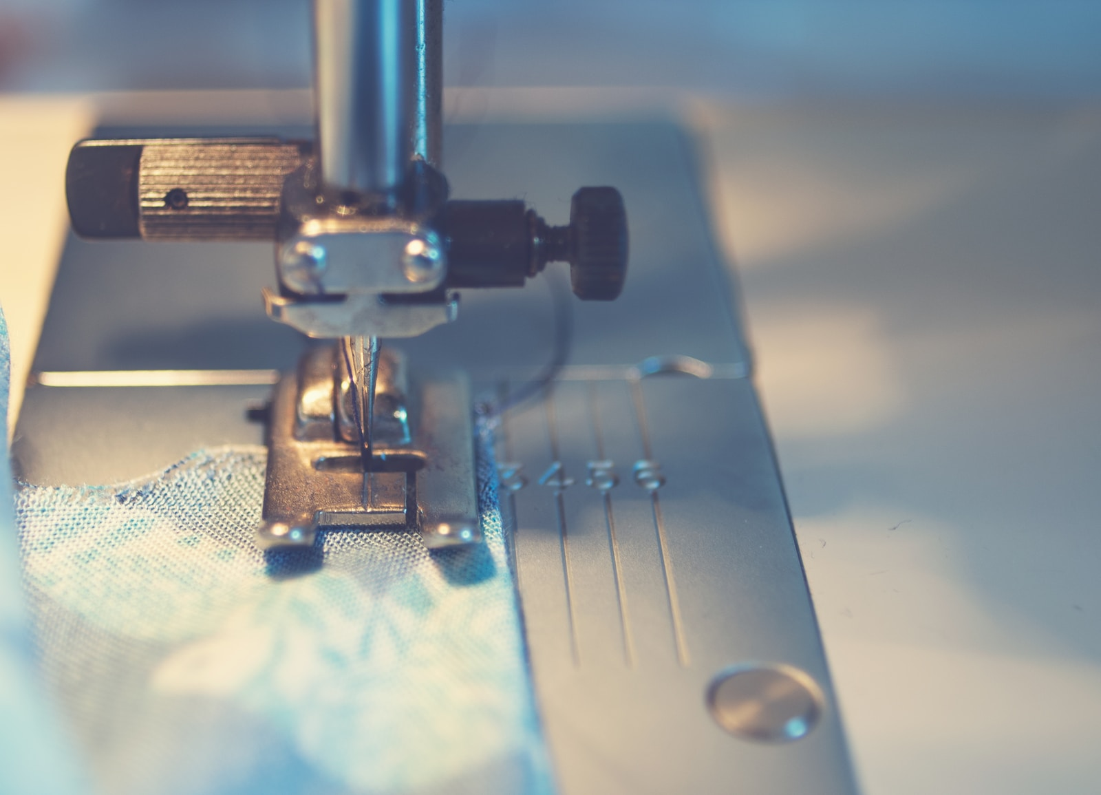blue textile under a sewing machine needle